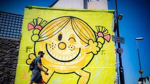 En mann går forbi et kunstverk av Will Blood på enden av en eiendom i Bedminster, Bristol, som 75 veggmaleriprosjektet når halvveis, og forskjellige graffitibiter sprøytes på vegger og bygninger over hele byen i løpet av sommeren