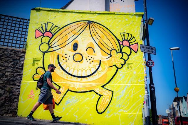 Un homme passe devant une œuvre d'art de Will Blood au bout d'une propriété à Bedminster, Bristol, comme le 75 le projet de peintures murales atteint la mi-parcours et divers graffitis sont pulvérisés sur les murs et les bâtiments de la ville au cours de l'été