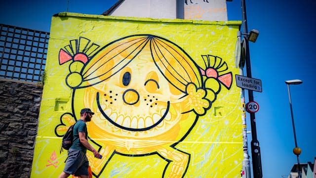 A man walks past an artwork by Will Blood on the end of a property in Bedminster, Bristol, as the 75 murals project reaches the halfway point and various graffiti pieces are sprayed onto walls and buildings across the city over the Summer