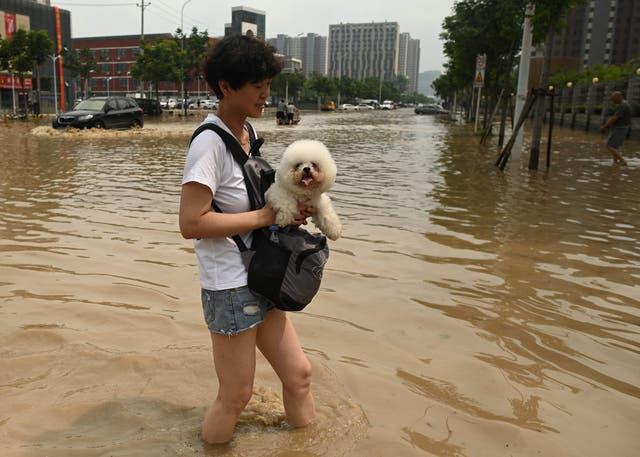 People wade through a flooded street following a heavy rain in Zhengzhou, in China's Henan province