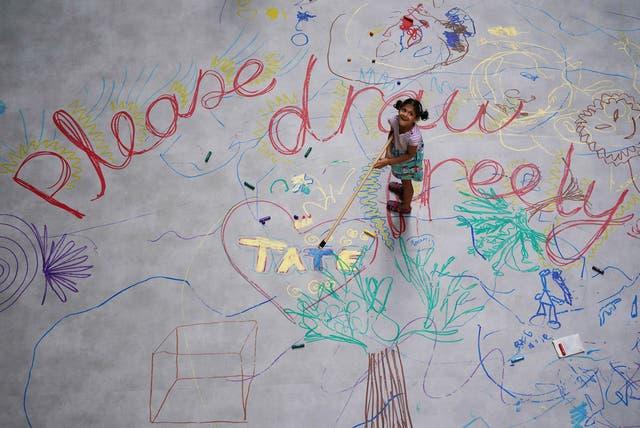 Les enfants interagissent avec Mega Please Draw Freely de l'artiste Ei Arakawa à l'intérieur du Turbine Hall de la Tate Modern de Londres, dans le cadre du nouveau programme gratuit d'activités inspirées de l'art pour les familles par UNIQLO Tate Play