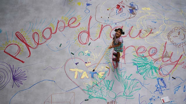 Children interact with Mega Please Draw Freely by artist Ei Arakawa inside the Turbine Hall at the Tate Modern in London, part of UNIQLO Tate Play the gallery's new free programme of art-inspired activities for families