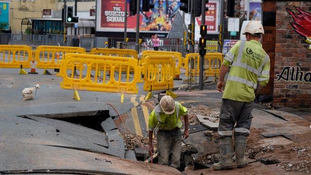 Forsyningsarbeidere inspiserer et 15x20ft synkehull på Green Lane, Liverpool, som mistenkes å være forårsaket av bristet vannledning