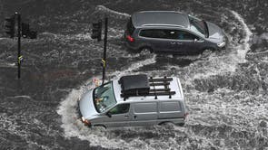 Vehicles drive through deep water on a flooded road in Nine Elms, 伦敦