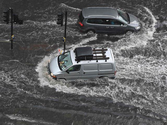 Voertuie ry deur diep water op 'n oorstroomde pad in Nine Elms, Londen