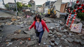 A woman walks in the rubble after flooding due to heavy rains in Dinant, Belgium, a week after more than 30 people were killed in floods in the country