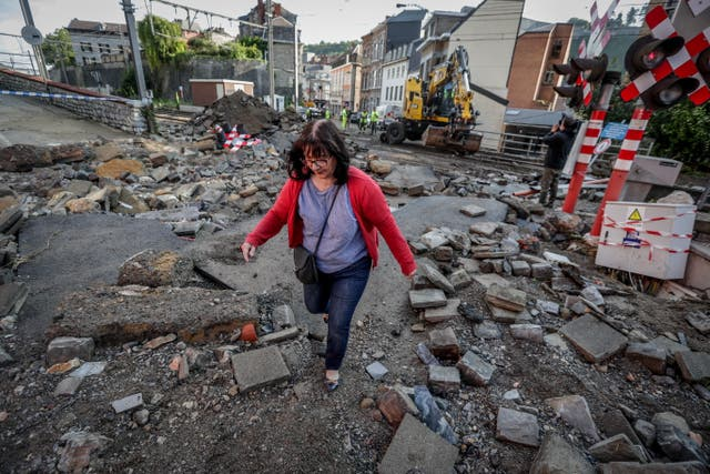 A woman walks in the rubble after flooding due to heavy rains in Dinant, 比利时, a week after more than 30 people were killed in floods in the country