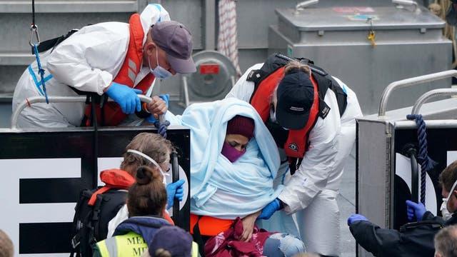 En kvinne blir hjulpet av offiserer i grensestyrken ettersom en gruppe mennesker som antas å være migranter blir brakt inn til Dover, Kent, ombord på et grensefartøy, etter en liten båthendelse i kanalen
