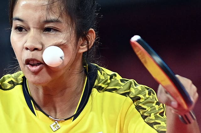 The ball hits Thailand's Orawan Paranang's face as she competes against Japan's Kasumi Ishikawa during her women's singles round 3 table tennis match at the Tokyo Metropolitan Gymnasium during the Tokyo 2020 奥运会