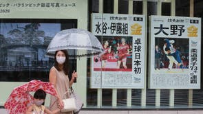 People wearing face masks to protect against the spread of the coronavirus walk past extra papers reporting on Japanese gold medalists at Tokyo Olympics