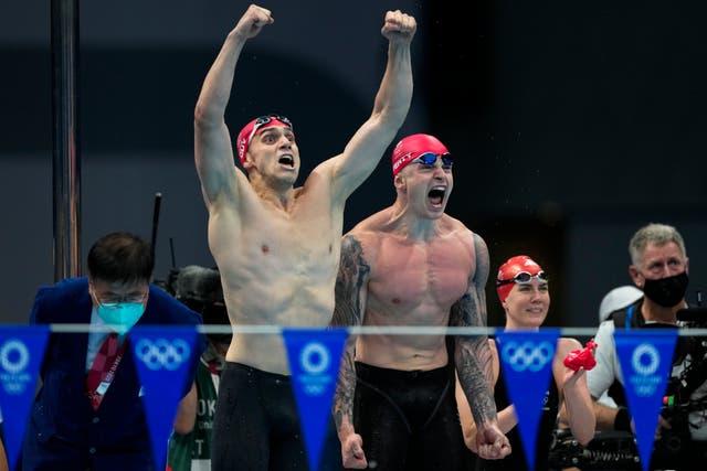 James Guy, Adam Peaty en Kathleen Dawson vier die verowering van die goue medalje in die gemengde 4x100m wisselslagaflosfinaal tydens die Olimpiese Spele in Tokio