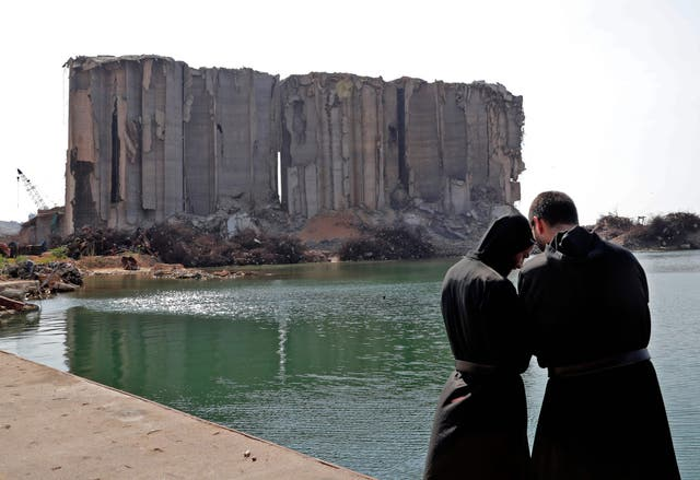 Maronite clergymen pray near damaged grain silos at the port of Lebanon's capital on the first anniversary of the blast that ravaged the port and the city