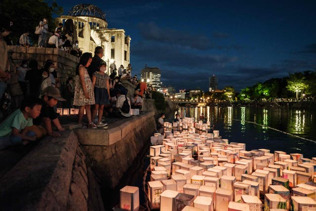 Members of local NPO release paper lanterns on Motoyasu River in front of beside the Hiroshima Prefectural Industrial Promotion Hall, as it was known before 1945, and now called the Atomic Bomb Dome, as the city marks the 76th anniversary of the world's first atomic bomb attack