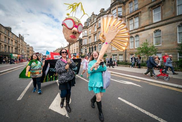 Mense uit die Glasgow Southside -gemeenskap neem deel aan die Govanhill -karnaval, 'n anti-rassistiese viering van trots, eenheid en die bydraes wat immigrante tot die gemeenskap in Govanhill gelewer het, by Queen's Park, Glasgow