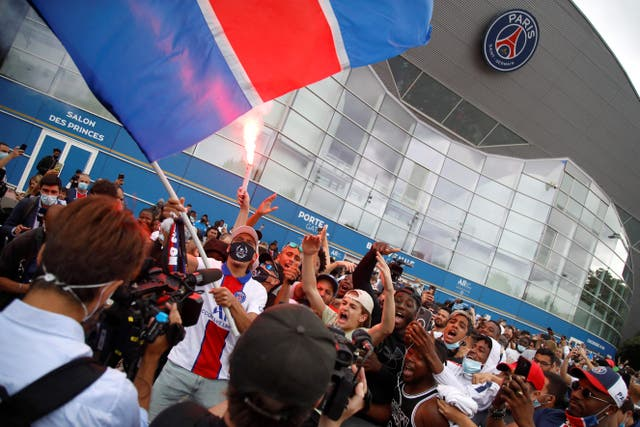 Supporters cheer outside French football club Paris Saint-Germain's Parc des Princes stadium in Paris after Argentinian football player Lionel Messi landed in Le Bourget airport to sign for the club