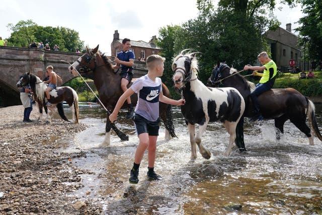 Kinders ry perd in die rivier Eden in Appleby, Cumbria, tydens die jaarlikse byeenkoms van reisigers vir die Appleby Horse Fair