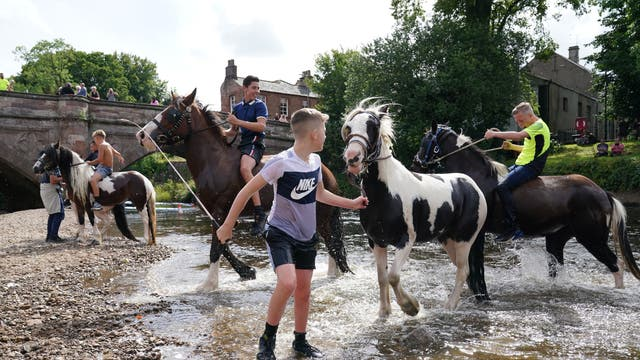 Les enfants montent à cheval dans la rivière Eden à Appleby, Cumbrie, lors du rassemblement annuel des voyageurs pour l'Appleby Horse Fair