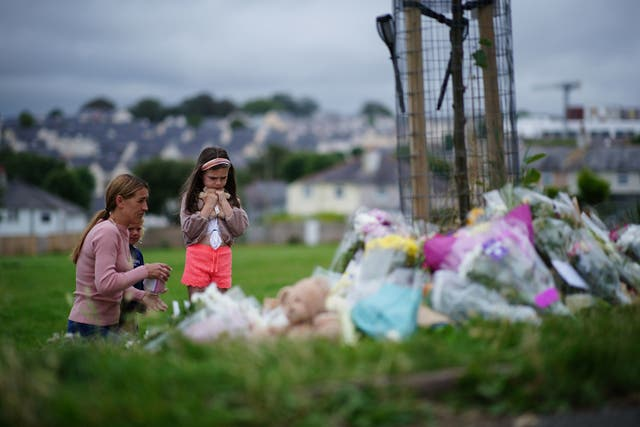 'N Vrou en twee jong meisies kyk na blomme -huldeblyke in Plymouth, waar ses mense woon, insluitend die oortreder, sterf aan skietwonde in 'n vuurwapenvoorval