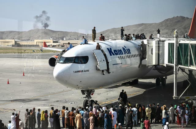 Afghan people climb atop a plane as they wait at the Kabul airport
