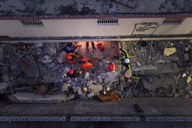 """Mexican firefighters known as """"Topos"""" work in the early morning hours in a search and rescue mission, amid the rubble from last week's 7.2 magnitude earthquake, in Les Cayes, 海地"""