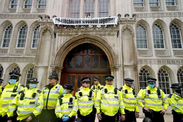 Polisiebeamptes vorm 'n tou voor die ingang van die Guildhall, Londen, waar betogers op 'n rand bo die ingang geklim het tydens 'n stadium van uitsterwing, 'n betoging