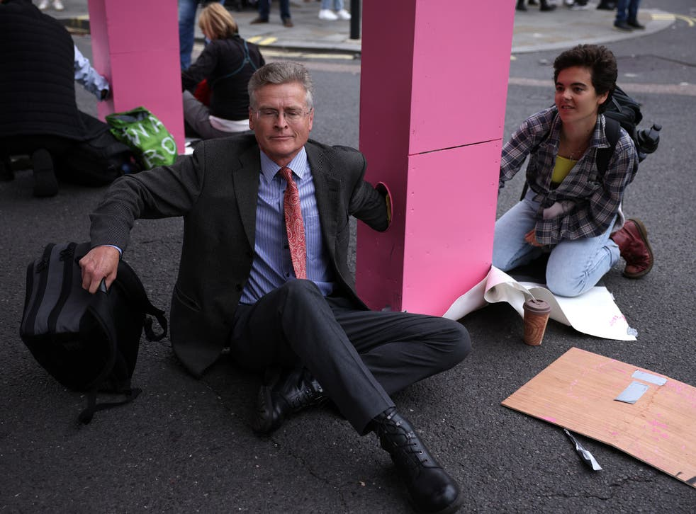 <p>Protestors lock their arms into the giant pink table to stop police from removing it </p>