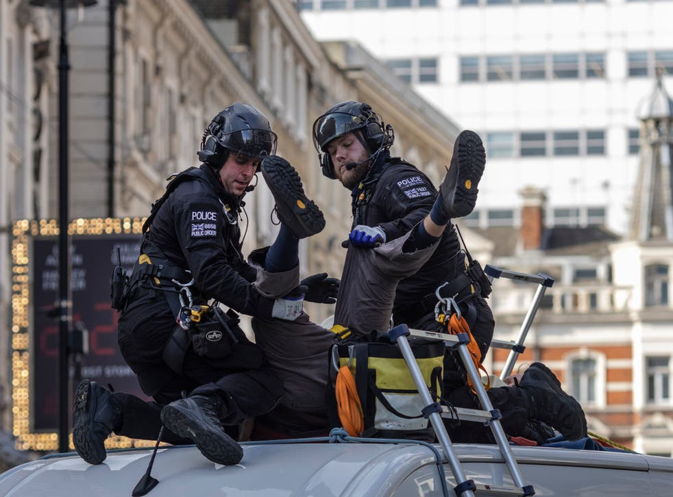 <p>An XR protester, who installed himself on top of a van near Covent Garden, is arrested by police</p>