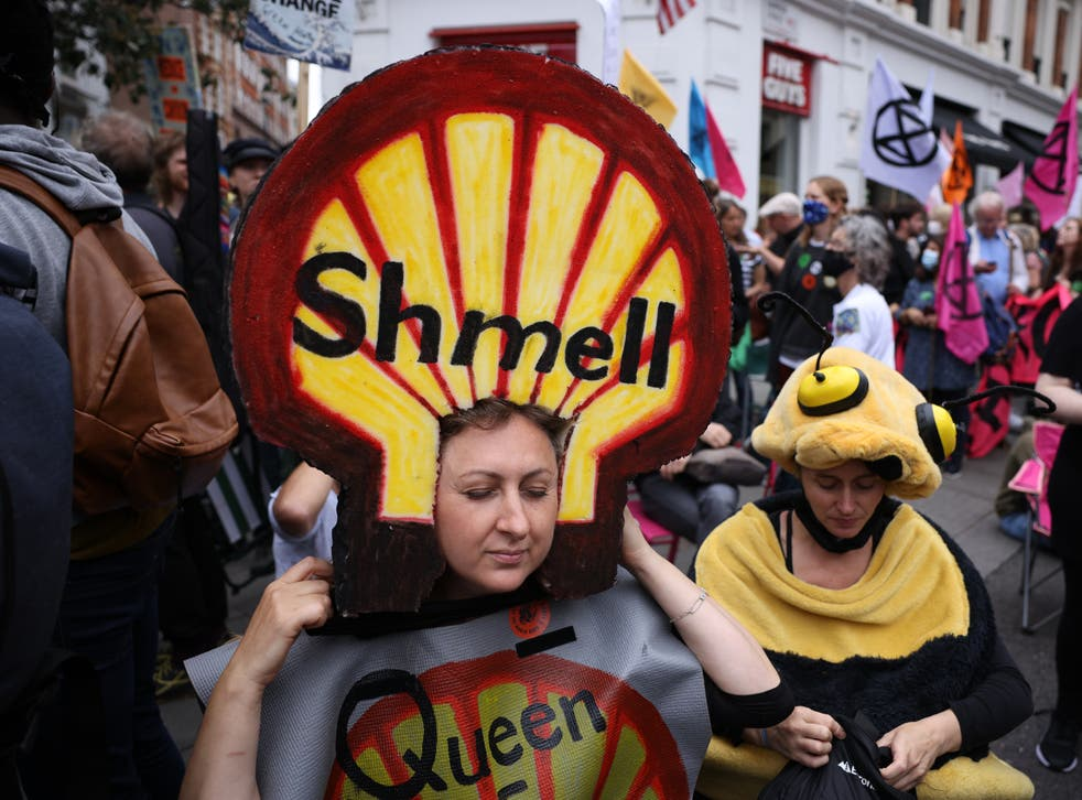 <p>Protesters dressed in costumes gather beneath XR's crisis-talks table</p>