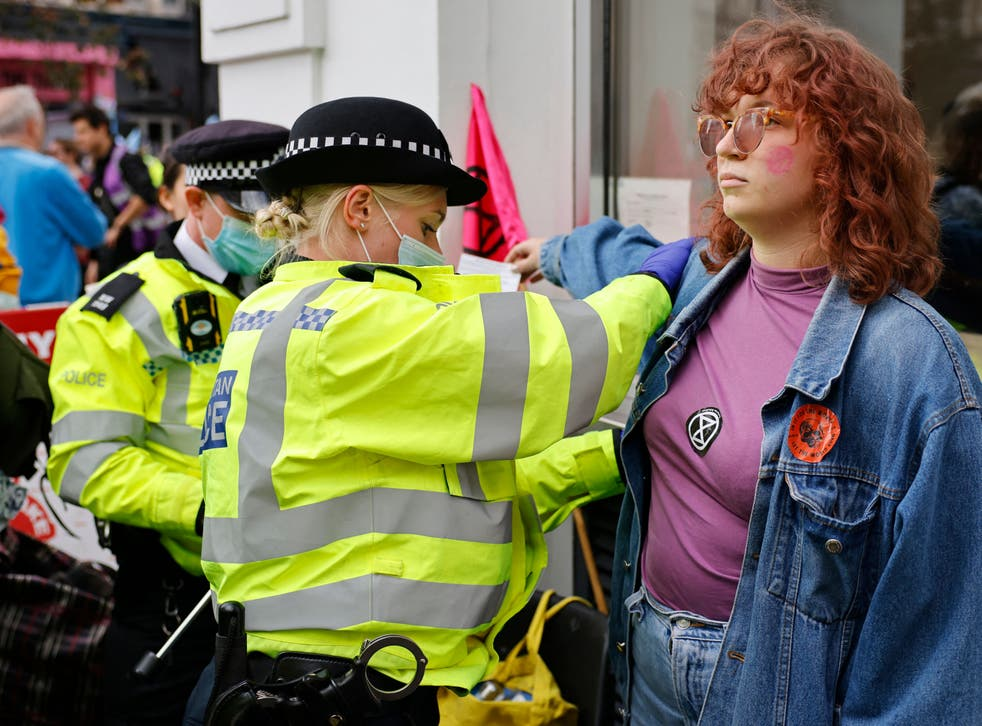 <p>A climate activist from XR is searched by police officers before being arrested </p>