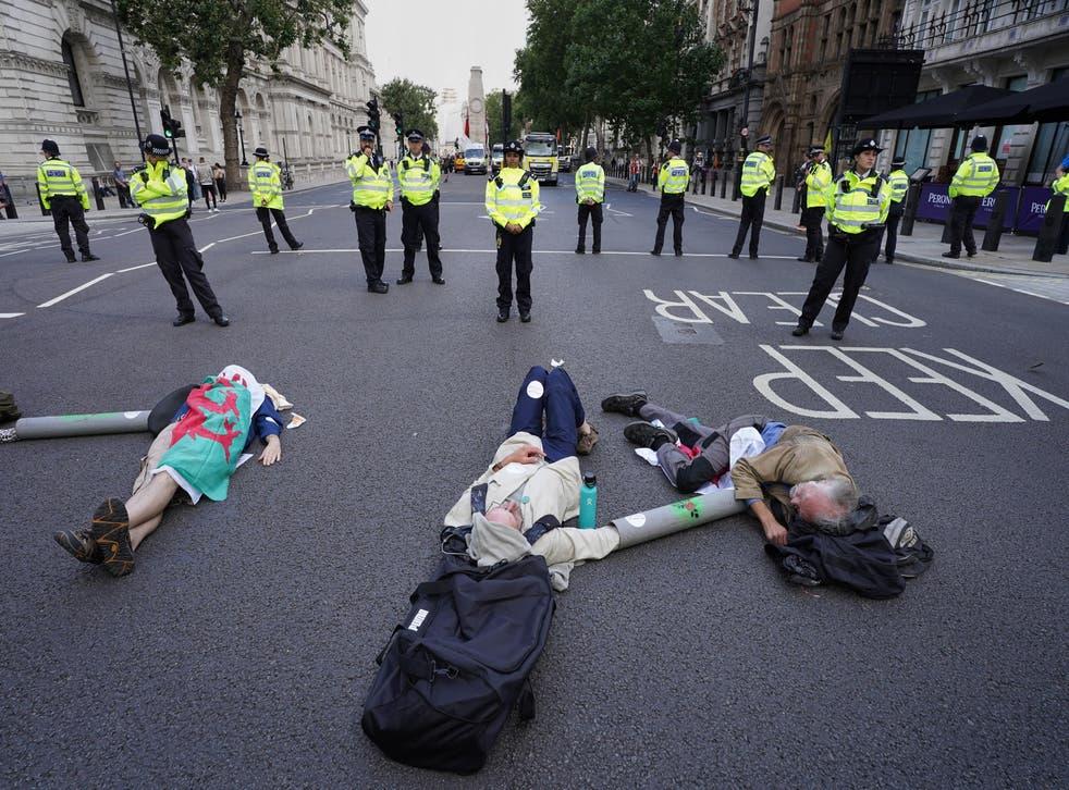 <p>Demonstrators from Extinction Rebellion lay on the floor in Whitehall, London</p>
