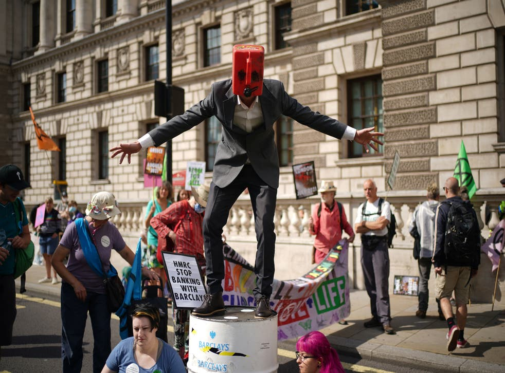 <p>A man wearing a petrol on top of a barrel joins climate activists from XR during a protest outside the offices of HM Revenue and Customs (HMRC)</p>