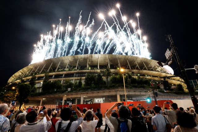 People take pictures of fireworks outside the stadium during the opening ceremony of the 2020 Paralympic Games in Tokyo