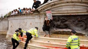 'N Extinction Rebellion -aktivis hou 'n plakkaat in 'n fontein omring deur polisiebeamptes, tydens 'n betoging langs die Buckingham -paleis in Londen