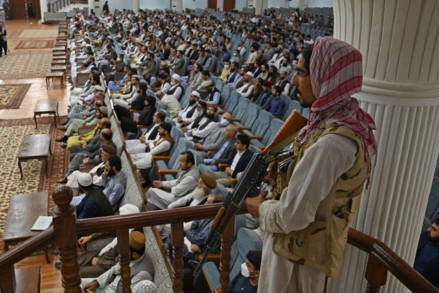 A Taliban fighter stands guard as Talibans acting Higher Education Minister Abdul Baqi Haqqani (not pictured) addresses a gathering during a consultative meeting on Taliban's general higher education policies at the Loya Jirga Hall in Kabu