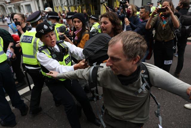 'N Polisiekantoor worstel met 'n betoger op Cromwellweg buite die Natural History Museum tydens 'n betoging deur lede van Extinction Rebellion in Londen
