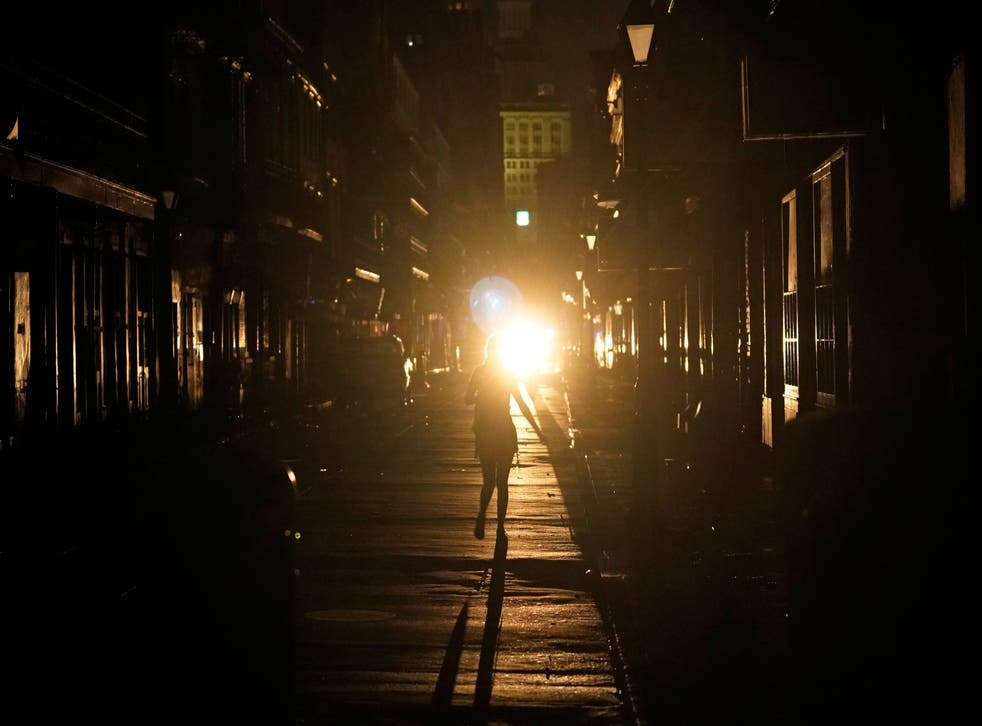 <p>A police officer patrols past woman walking along Bourbon Street</磷>