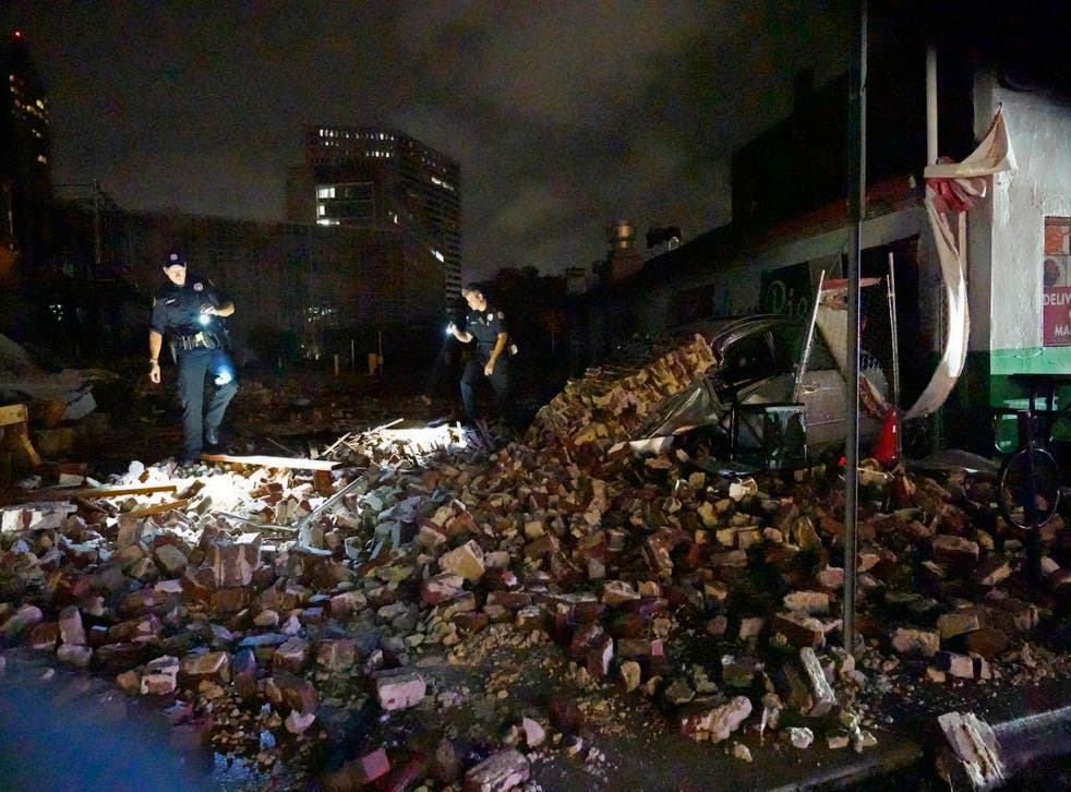 <p>New Orleans Police detectives look over debris from a building that collapsed</磷>