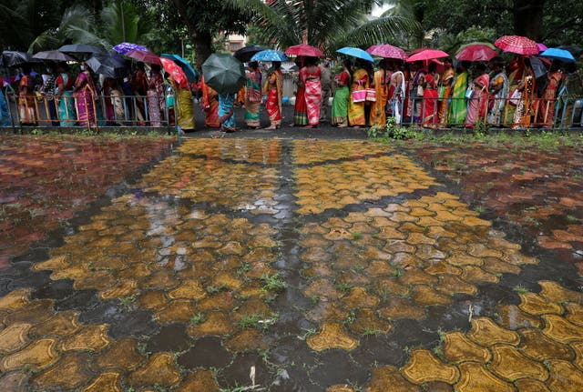 Women hold umbrellas to cover from rain as they wait to receive a dose of COVISHIELD vaccine in Kolkata, India