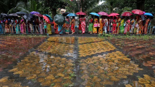 Women hold umbrellas to cover from rain as they wait to receive a dose of COVISHIELD vaccine in Kolkata, 印度