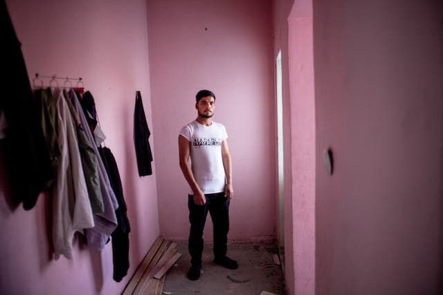 Dost Mohammad (21), an Afghan refugee from Bagalan poses for a portrait in the abandoned building he lives with  Abdullah Matin (17)
