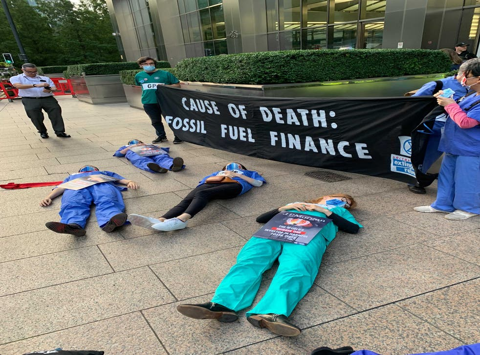 <p>Protesters dressed in their scrubs lay on the floor and held banners in Canary Wharf</p>