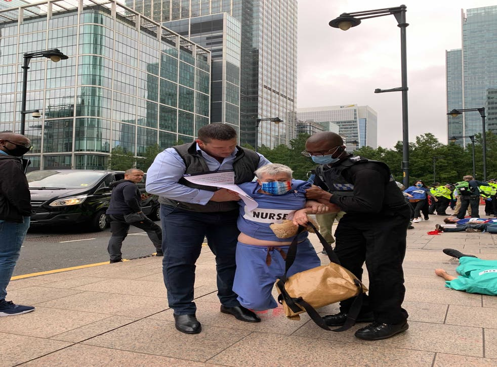 <p>This woman dressed in nursing scrubs was led away by security </p>