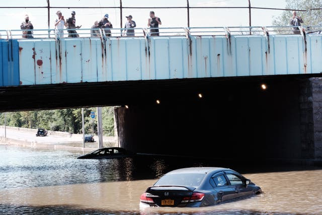People look at cars abandoned on the flooded Major Deegan Expressway following a night of extremely heavy rain from the remnants of Hurricane Ida, in the Bronx borough of New York City