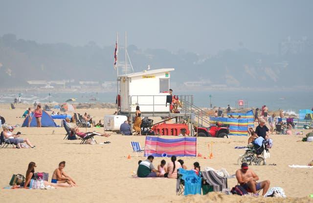 Mense geniet die warm weer op Sandbanks -strand, Poole