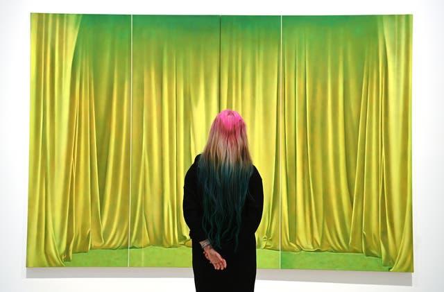 """'N Galerywerknemer poseer vir fotograwe langs 'n skildery met die titel """"Prairie"""" van die Britse kunstenaar, Louise Giovanelli tydens die uitstalling 'Mixing it up: Skilder dit in die Hayward Gallery in Londen"""