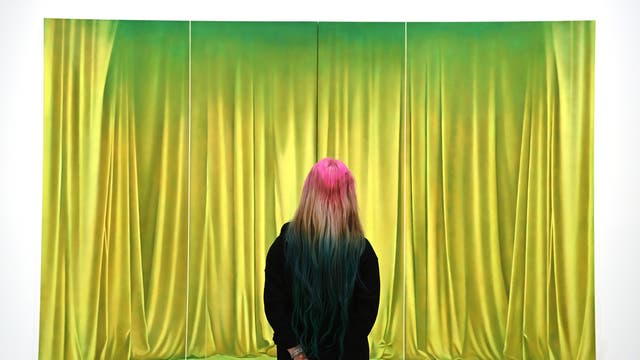 """A gallery employee poses for photographers next to a painting entitled """"Prairie"""" by British artist, Louise Giovanelli during the exhibition 'Mixing it up: Painting it up' at the Hayward Gallery in London"""