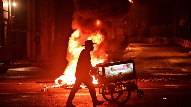 A vendor pushes a cart of sugarcane juice past a fire at a demonstration in Bangkok as activists call for the resignation of Thailand's Prime Minister Prayut Chan-O-Cha over the government's handling of the Covid-19 crisis