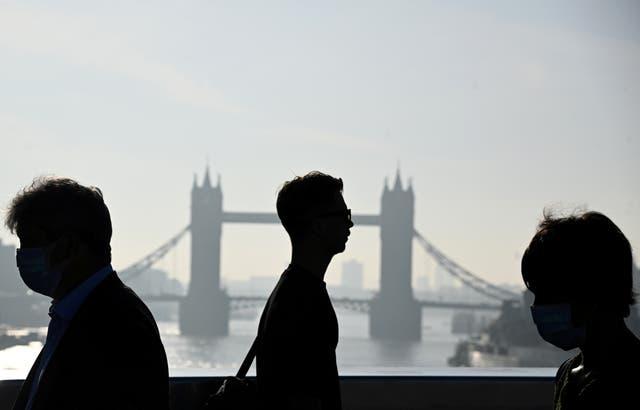 Werkers steek die London Bridge oor tydens die oggendspit in Londen