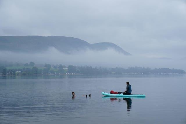 Mense roei op 'n mistige oggend in Ullswater, die tweede grootste meer in die Lake District, Cumbria