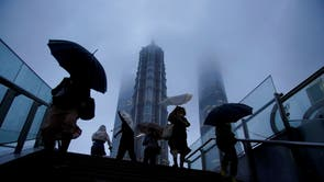 People hold umbrellas amid rainfall as Typhoon Chanthu approaches, in Shanghai, Chine
